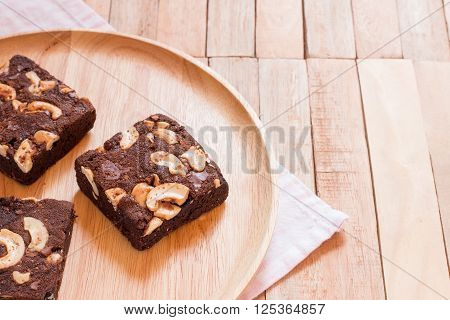 Chocolate brownie cake served on wooden plate.