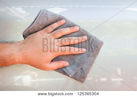Cleaning car with microfiber cloth by a man's hand.