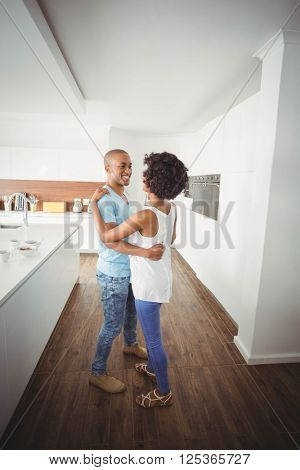 Happy couple dancing in the kitchen at home