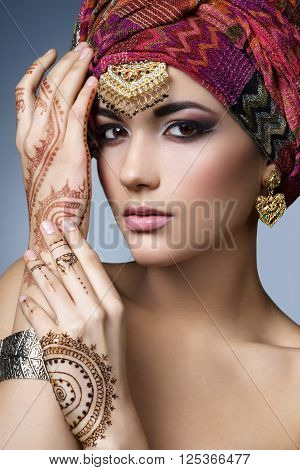 Beautiful fashion east woman portrait with oriental accessories- earrings bracelets and rings. Indian girl with henna tattoos and beauty jewels. Hindu model with perfect makeup. India. Asia