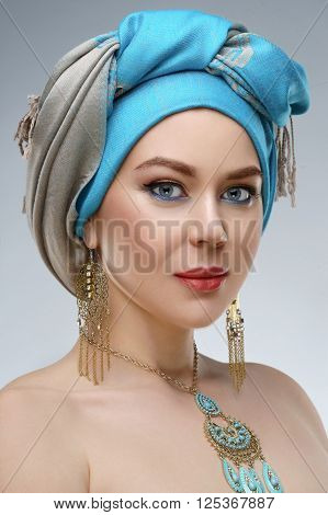 Beautiful fashion east woman portrait with oriental accessories- earrings bracelets and rings. East woman with henna tattoos and beauty jewels. Model with perfect make-up.