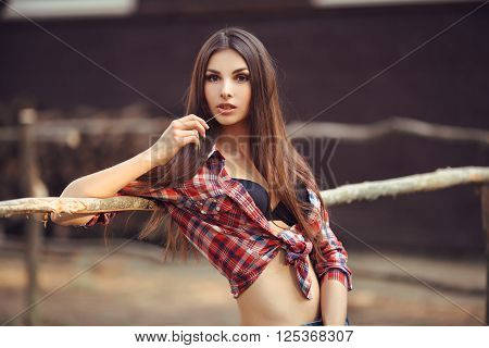 Portrait of young hot woman. Cowgirl style outdoors