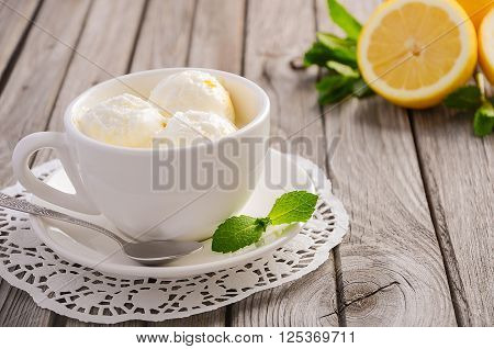 Lemon ice cream in white cup on rustic wooden background, selective focus, copy space