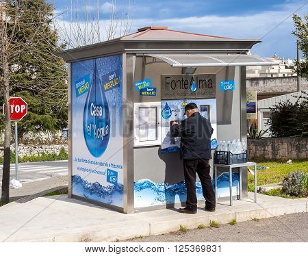 Martina Franca Italy - March 1 2016: The Water Houses deliver quality public water still or sparkling chilled or at room temperature. A man fills bottles of water for household consumption