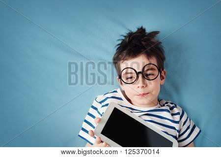 seven years old child lying with tablet on blue background