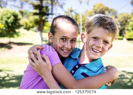 Portrait of Siblings embracing each other in park