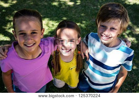Portrait of happy children standing with arm around in park
