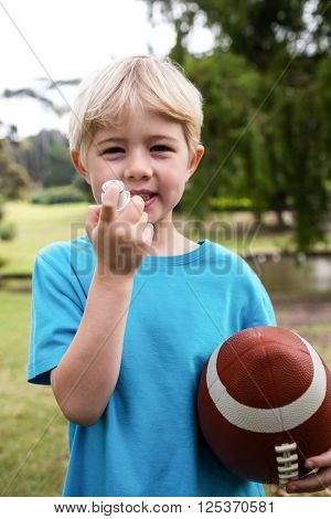 Boy with an american football using an asthma inhaler in the park