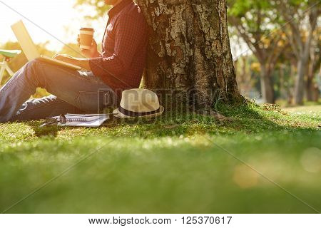 Cropped image of man sitting under the tree with coffee and laptop