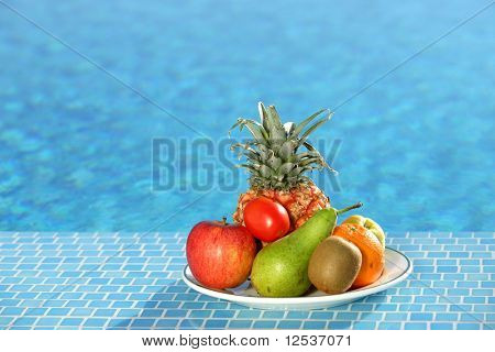Plate of fruits next to a swimming pool