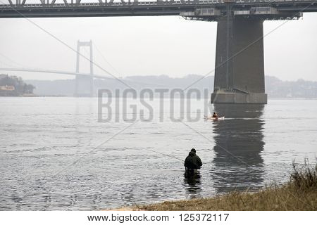 Fisherman in Little Belt - Little Belt Bridge in the background. - Middelfart in Denmark.