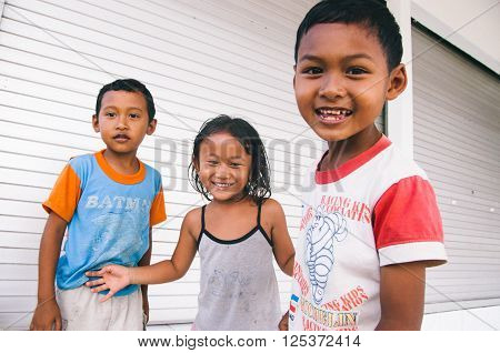 UBUD,INDONESIA - JULY 27:Unrecognizable Balinese children having fun while looking at the camera. on july 27th of 2009 in Bali Indonesia. Local children can be very intrigued and curious about the foreign people visiting their village.