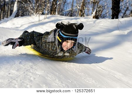 Little boy riding with hills on sleds on winter weather