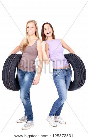 Two women holding car wheels and laughing. Isolated
