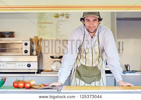 Young male entrepeneur standing confidently in his food stall where he makes and sells takeaway food