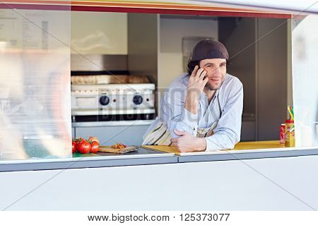 Male entrepeneur leaning on the counter and talking on the phone in his food stall where he makes and sells takeaway food