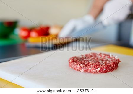 High quality raw hamburger patty sitting ready on a white board waiting for seasoning and cooking, while chef's hands prepare other ingredients in the background