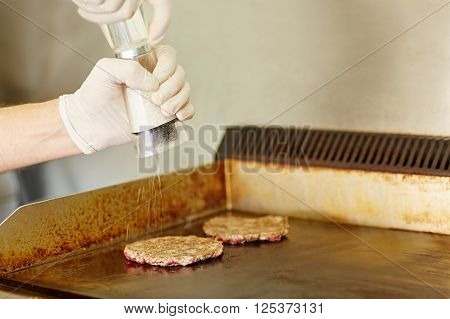 Cropped shot of gloved cook's hands grinding salt onto two hamburger patties to season them while they are frying on the grill