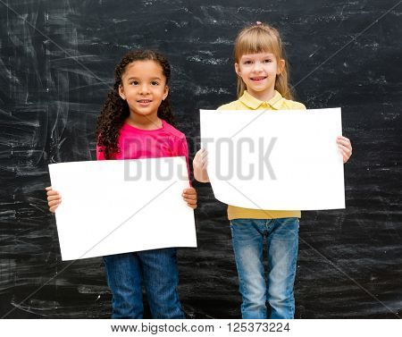 two pretty little girls with blank paper in hands