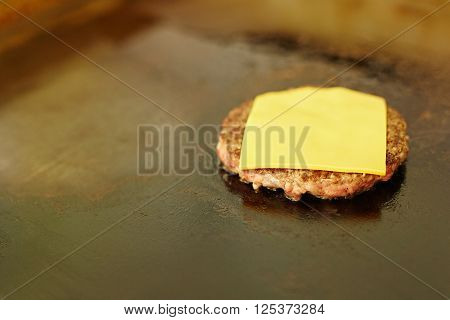 Succulent hamburger patty frying with a slice of fresh cheese melting on top of it