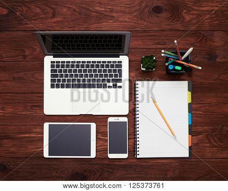 Laptop, tablet, smartphone, plant, pencil holders and notebook with pencil on a wooden table