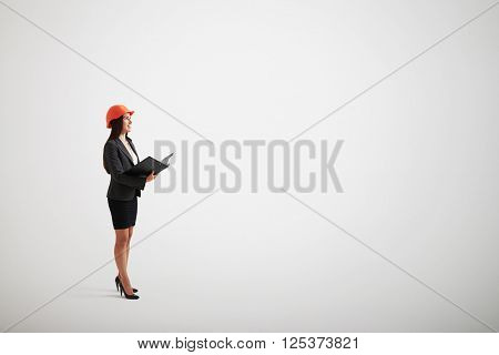 Standing woman in formal wear and construction helmet with a folder in her hands