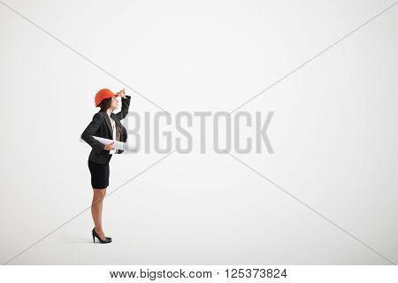 Serious looking woman in formal wear and construction helmet holding blueprints in her hand and looking upwards