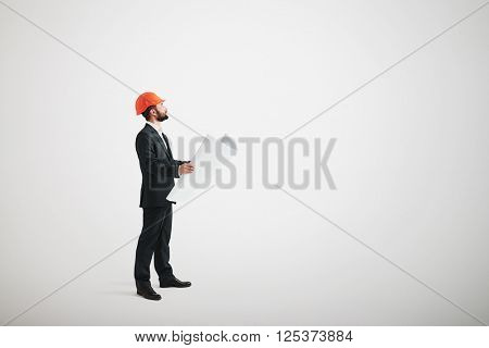 Side view of bearded man in a formal wear and in a hard hat holding blueprints and looking upwards