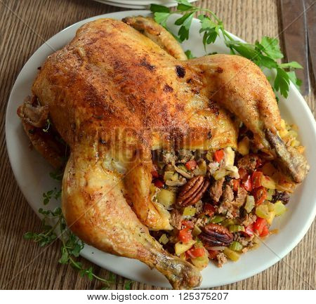Roasted Chicken; Stuffed with toasted pecans, celery, carrots, bread. Close up from above.