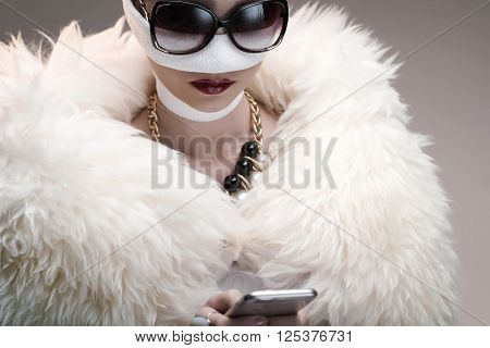 Portrait of diva after rhinoplasty reading text message