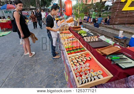 LAMPANG, THAILAND - FEBRUARY 19, 2016: Customers of street market watching food appetizers and sushi with seafood on fast-food court on February 19, 2016. Population of Lampang is near 59000 people