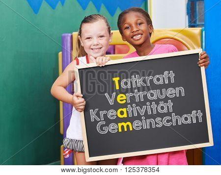 Children holding blackboard with team concept in German (drive, trust, creativity, community)