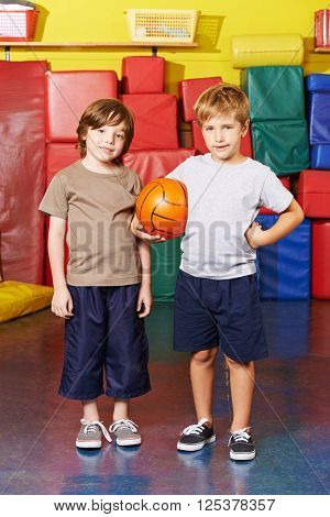 Two boys standing with basketball in gym of an elementary school