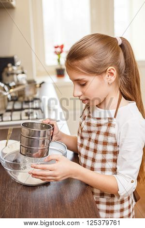 Young Teenage Girl Sieving Flour Through The Sieve