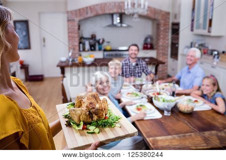 Woman holding a tray of roasted turkey and family dining in background