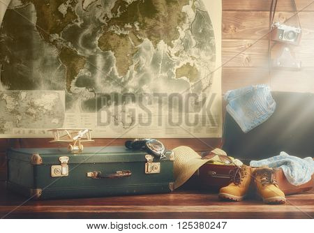 travel preparation. suitcase, clothing and accessories in vintage style on the background of wooden wall and maps of the world.