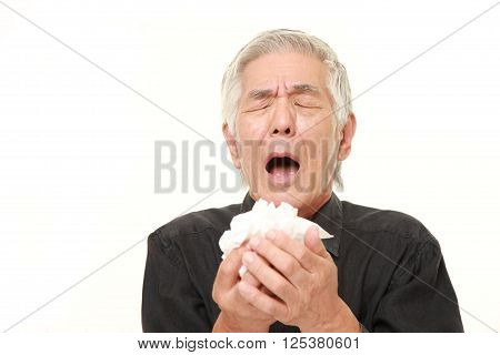 senior Japanese man with an allergy sneezing into tissue