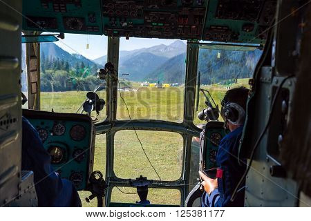Helicopter Cockpit During Take Off from Landing Camp at Remote Are of Kyrgyzstan Throw Window Pilot Arms