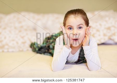 A cute little girl lying on the floor while pulling a face