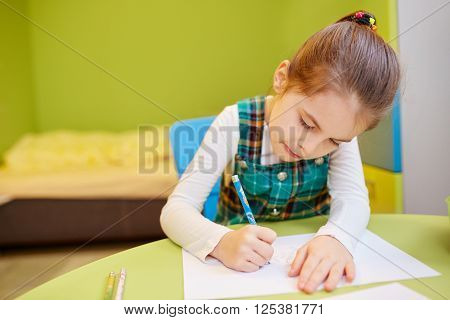 A little girl drawing  in her room