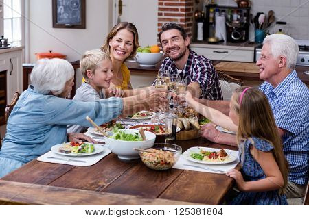 Multi-generation family toasting glass of wine while having mea
