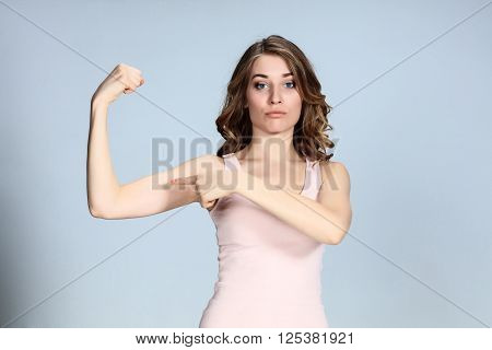 The young woman showing her muscles on gray background. Strength and power concept