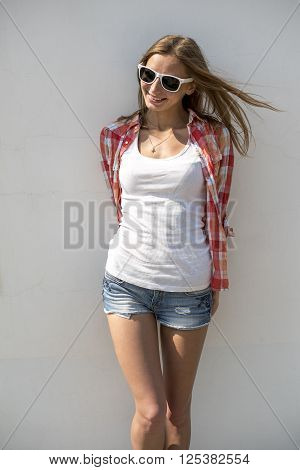 Bright sexy, beautiful young girl, wearing glasses posing in front of a white wall, in short shorts and white T-shirt