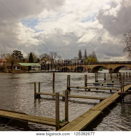 Empty wooden boat moorings and bridge across the Thames river at Henley, Oxfordshire, England