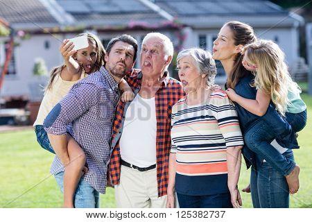 Happy multi-generation family taking a selfie in garden