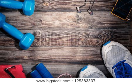 Sport stuff on wooden table, top view. Light spot in center of wooden table with empty space for text, logo, or something else.