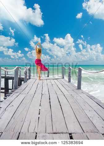 Woman walking on the wooden deck at the tropical resort