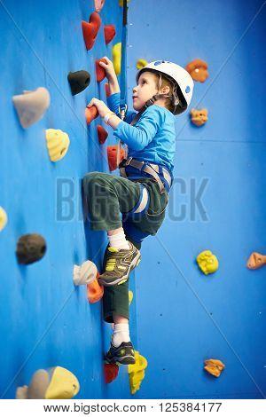 Little Boy Is Climbing On Blue Wall