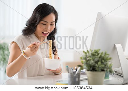 Chinese female business executive eating noodle soup at her workplace