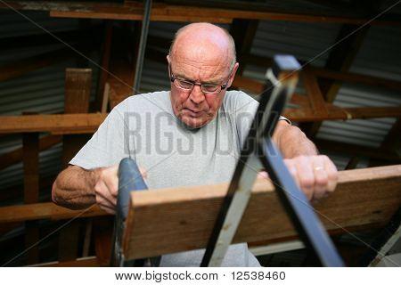 Alter Mann Schleifen einem Holzbrett